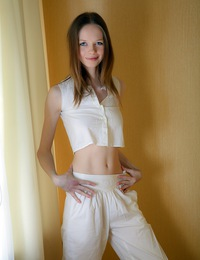 A horny skinny teenage chick undresses her perfect body